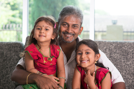 Happy Indian family at home. Asian father and daughters sitting on sofa smiling. Parent and children indoor lifestyle.