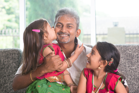 Happy Indian family at home. Asian girl kissing her father, sitting on sofa. Parent and children indoor lifestyle. photo