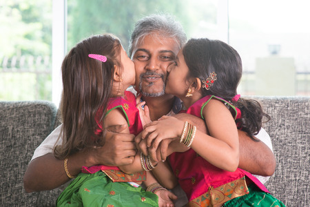 single father: Happy Indian family at home. Two cute Asian girls kissing father, sitting on sofa. Parent and children indoor lifestyle.
