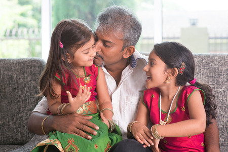 Happy Indian family at home. Asian father kissing her daughter, sitting on sofa. Parent and children indoor lifestyle. photo