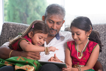 home schooling: Indian family at home. Asian father and children using digital tablet computer, sitting on sofa, home schooling concept.