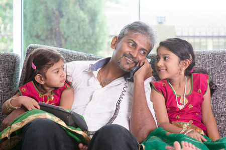 house call: Husband making a phone call to wife while taking care of children at home. Asian Indian family at home.