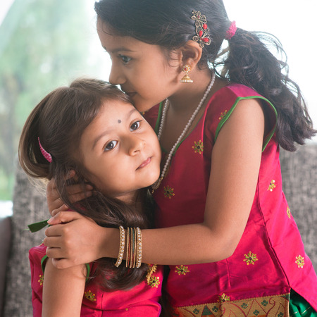Indian girl kissing her younger sister with love. Asian family at home. Beautiful daughters in traditional India sari. photo