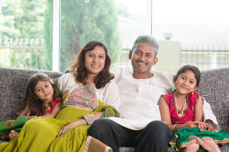 Indian family at home. Asian parents and children living lifestyle, sitting on couch indoor smiling happily. photo
