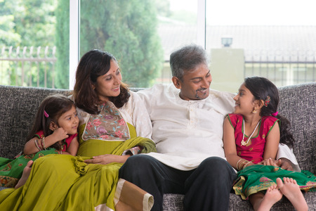 chit: Happy Indian family at home. Asian parents chit chatting with their kids, sitting on sofa. Parents and children indoor lifestyle.
