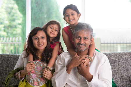 indian happy family: Happy Indian family at home. Asian parents piggyback their kids, sitting on sofa. Parents and children indoor lifestyle. Stock Photo