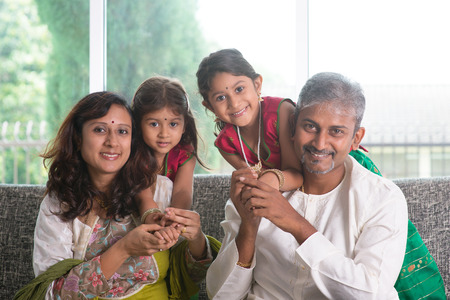 Happy Indian family at home. Asian parents with their kids, sitting on sofa. Parents and children indoor lifestyle. photo