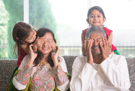 Indian family living lifestyle at home. Cute girls in traditional sari costume covering father and mother eyes. Asian parents and children.