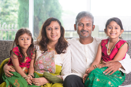 Happy Indian family at home. Asian parents and children living lifestyle, sitting on couch indoor happily. photo