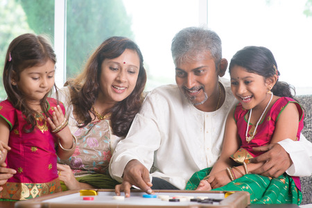 Happy Asian Indian family playing carrom game at home. Parents and children indoor lifestyle. photo