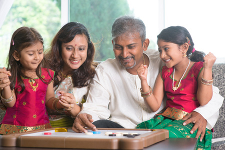 indian woman traditional: Asian Indian family playing carrom game at home. Parents and children indoor lifestyle.