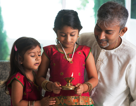 Indian family in traditional sari celebrate diwali or deepavali at home. Little girl hands holding oil lamp during festival of light. Stock Photo