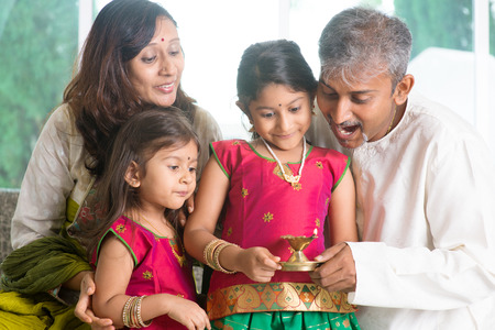 asian and indian ethnicities: Indian family in traditional sari celebrate diwali or deepavali at home, little girl hands holding oil lamp with father indoor. Stock Photo