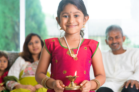 Indian family celebrate diwali or deepavali at home, little girl with traditional clothing sari, hands holding oil lamp indoor. Stock Photo