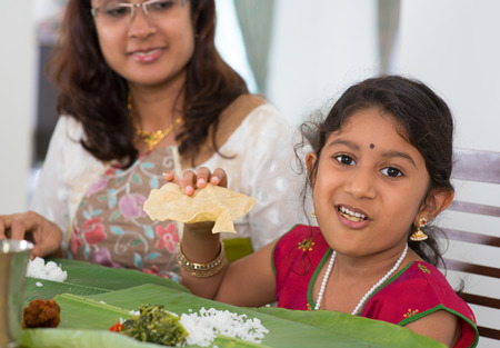 Indian family dining at home. Little girl eating snack papadum. India culture. photo