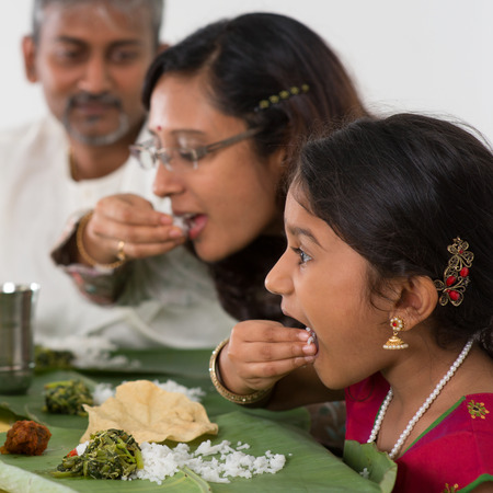 people together: Indian family dining at home. Candid photo of Asian people eating rice with hands. India culture.