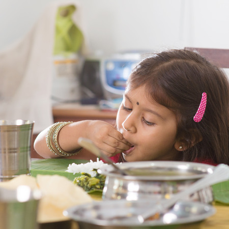 family dining: Indian family dining at home. Candid photo of Asian child self feeding rice with hand. India culture. Stock Photo