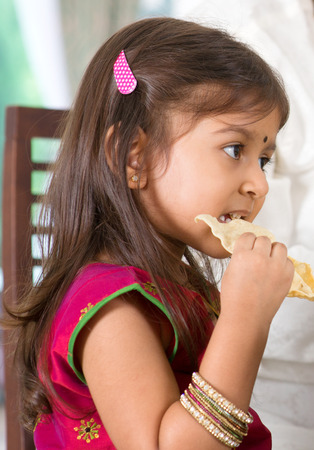 family dining: Indian family dining at home. Candid photo of Asian child self feeding snack papadum. India culture.