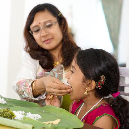 indianen: Indische familie dineren thuis. Candid foto van Aziatische moeder voeden rijst kind met de hand. India cultuur.