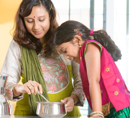 Asian family cooking food together at home. Indian mother and child preparing meal in kitchen. Traditional India people with sari clothing. photo