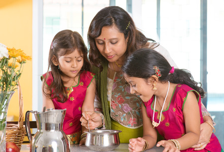 Asian family cooking food together at home. Indian mother and children preparing meal in kitchen. Traditional India people with sari clothing. photo