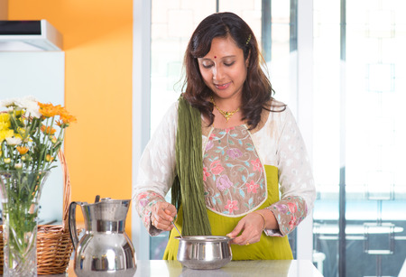 Indian woman preparing meal inside kitchen. Asian female cooking food at home. photo