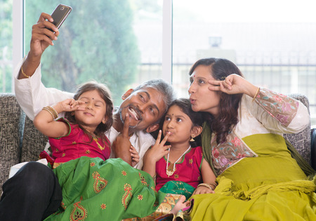 taking: Asian Indian family selfie or self photograph at home. Parents and children indoor lifestyle.