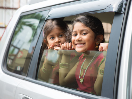 indian woman traditional: Asian Indian family going to a vacation. Happy children sitting inside car with window open looking out.