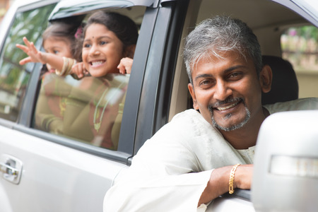 Indian family sitting in car ready to trip. Asian parent and children lifestyle. photo