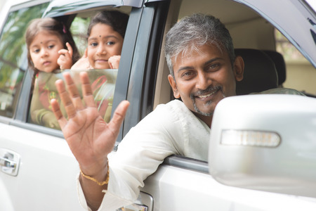 indian happy family: Indian family waving hands and saying goodbye, sitting in car ready to trip. Asian family lifestyle. Stock Photo