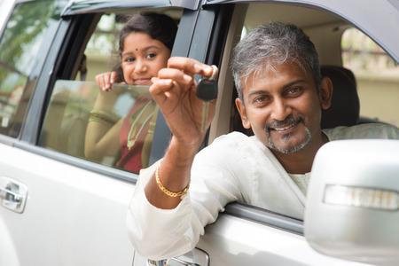 chicas comprando: Hombre indio compra el nuevo coche y mostrando la clave, sentado en el coche. El estilo de vida de la familia asiática. Foto de archivo