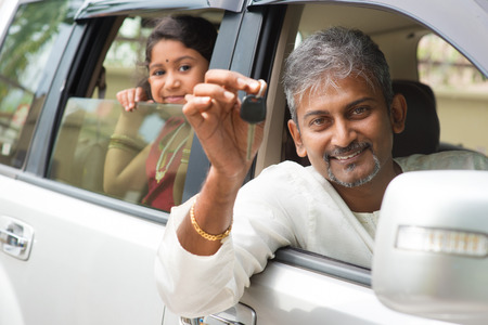 Indian man buying new car and showing the key, sitting in car. Asian family lifestyle.