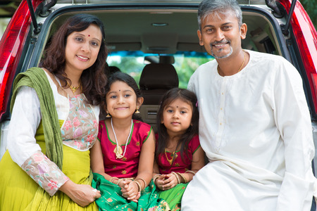 Happy Asian Indian family sitting in car, ready to summer vacation. photo