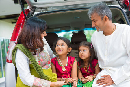 Happy Asian Indian family sitting in car talking and smiling happily, ready to summer vacation. photo
