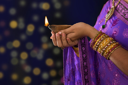 Diwali or festive of lights. Traditional Indian festival, woman in sari hands holding oil lamp, with defocus light .