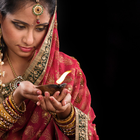 Beautiful Indian woman hands holding diya oil lamp, celebrating diwali festive of lights, traditional sari prayer isolated on black with copy space on side.