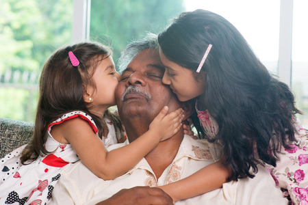 grandpa: Portrait Indian family at home. Grandchildren kissing on grandparent face. Asian people living lifestyle.