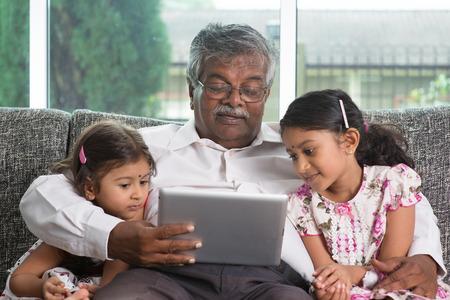 Portret Indische familie thuis. Grootouder en kleinkinderen met behulp van digitale tablet-computer. Aziatische mensen die levensstijl. Stockfoto