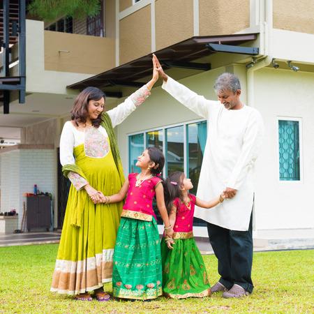 zakelijk: Ouders vormen huis dakvorm boven kinderen. Mooie Aziatische Indiase familie portret glimlachend en permanent buiten hun nieuwe huis.