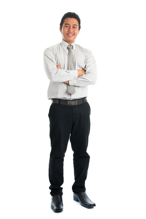 Full body of handsome Asian young male in casual business attire, smiling confidently with arms crossed, standing isolated on white .