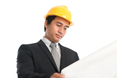 Close-up of an Asian young man wearing a hardhat looking at blueprint paper, standing isolated on white . photo