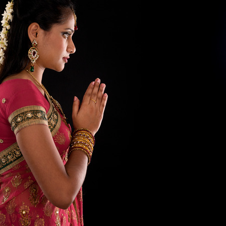 Beautiful Indian girl in greeting pose, traditional sari prayer isolated on black with copy space on side. photo