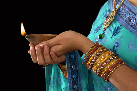 lady with the lamp: Diwali or festive of lights. Traditional Indian festival, woman in sari hands holding oil lamp, copy space at side.