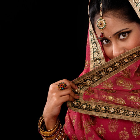 Portrait of beautiful mystery young Indian woman covering her face by veil, looking at camera, copy space at side, isolated on black .