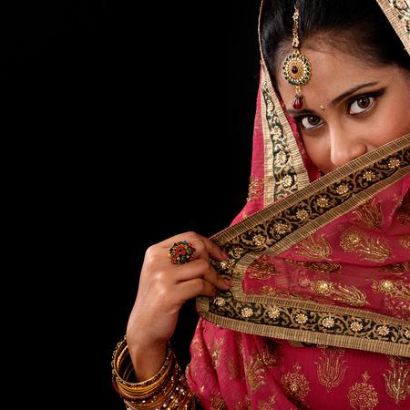 indianen: Portret van mooie mysterieuze jonge Indiase vrouw die haar gezicht met sluier, kijkend naar de camera, kopie ruimte aan de zijkant, geïsoleerd op zwart. Stockfoto