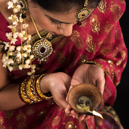 Beautiful Indian female hands holding diya oil lamp, celebrating diwali festive of lights, traditional sari prayer isolated on black with copy space on side. Stock Photo