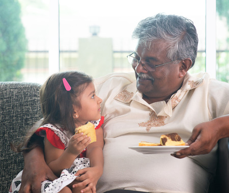 Portrait Indian family at home. Grandparent and grandchild eating cake. Asian people living lifestyle. Grandfather and granddaughter.