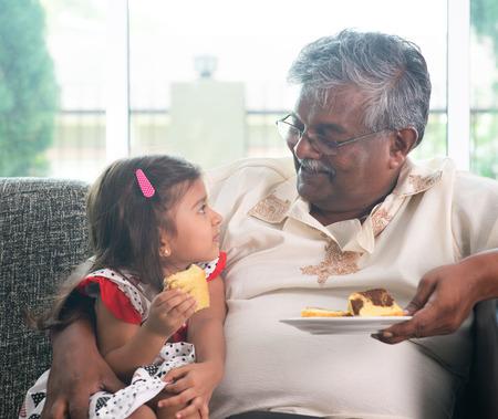 persona de la tercera edad: Retrato de la familia india en casa. Abuelo y nieto come la torta. Los asi�ticos del estilo de vida que viven. Abuelo y nieta.