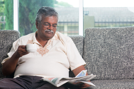 Asian Indian senior adult drinking coffee while reading news paper sitting on sofa at home in morning, elderly retirement indoor living lifestyle. photo