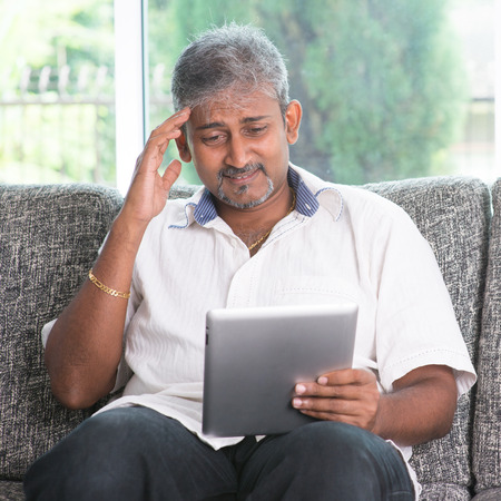 Portrait of middle aged Indian man headache while reading on digital tablet computer at home. photo
